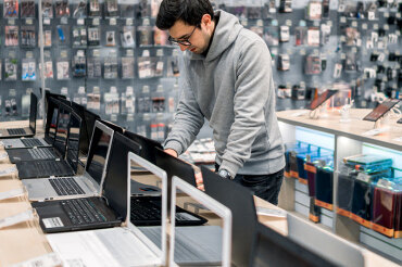 Man browsing laptop computers for purchase