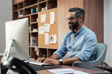 Man happy to use his computer in the workplace