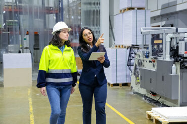 Manager walking through manufacturing factory with a worker and a tablet